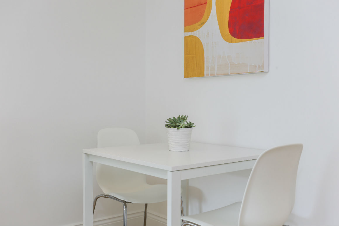 White dining table and two chairs in Kings Cross 1 bedroom apartment