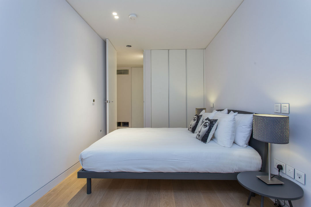 Double bed and built in wardrobe in a one bedroom apartment
