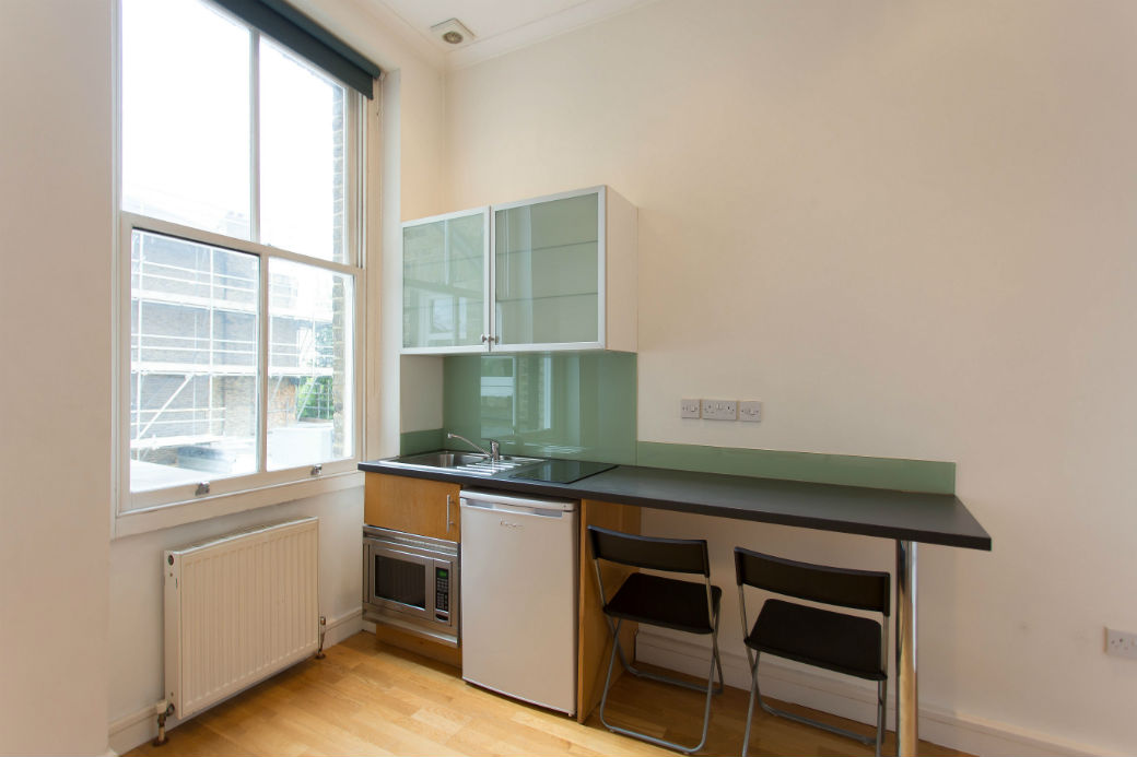 Kitchenette with a microwave, fridge, hob and two chars in a studio apartment
