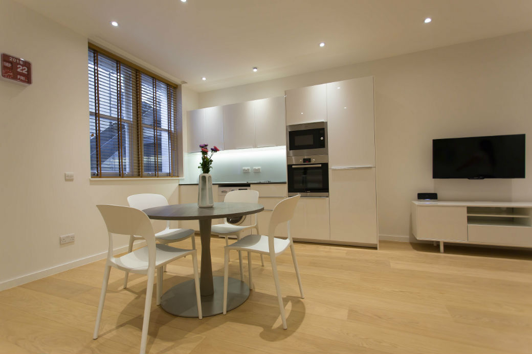 Very modern white kitchen and dining table in a studio flat in Fitzrovia