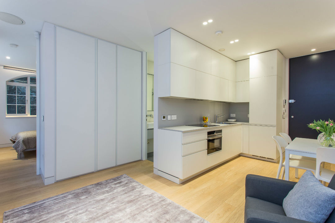 One bedroom apartment with built in storage space, modern kitchen and armchairs