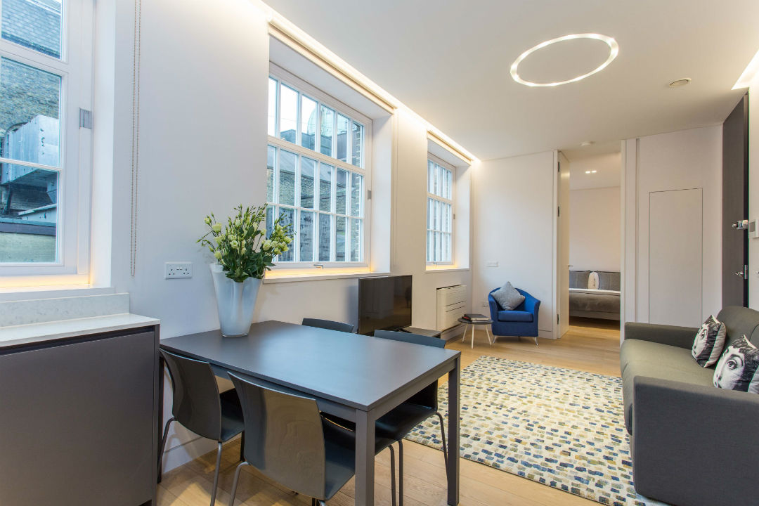 Open plan reception room with big windows, sofa, dining table and flat screen TV in Mornington Crescent London